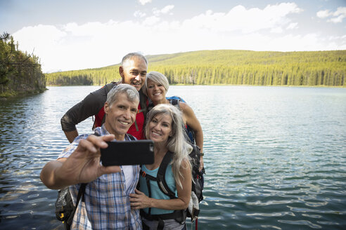 Mature couples hiking, taking selfie with camera phone at lakeside, Alberta, Canada - HEROF11955