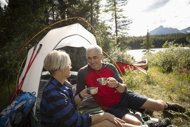 Mature couple talking and drinking coffee by tent at sunny forest campsite, Alberta, Canada - HEROF11967