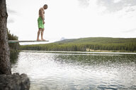 Mature man on diving board above lake, Alberta, Canada - HEROF11988
