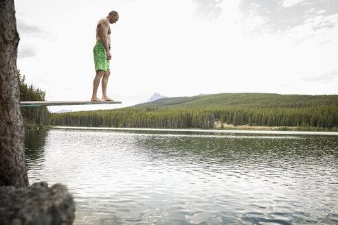 Mature man on diving board above lake, Alberta, Canada - HEROF11988
