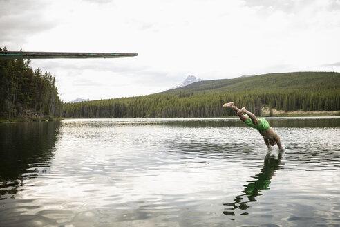 Mature man diving into lake, Alberta, Canada - HEROF11991