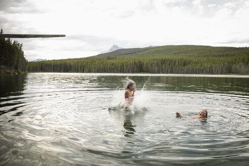 Mature women diving and swimming in lake, Alberta, Canada - HEROF11994