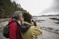 Active senior couple backpacking, using binoculars on rugged beach - HEROF11997