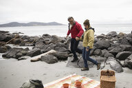 Active senior couple enjoying picnic, walking on rocks on rugged beach - HEROF12003
