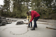 Affectionate active senior couple drawing heart-shape in wet sand on rugged beach - HEROF12006