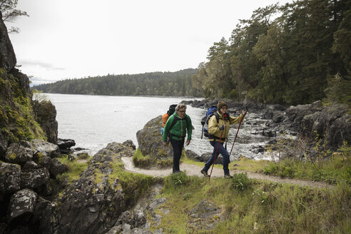 Active senior couple backpacking on cliff trail overlooking ocean - HEROF12015