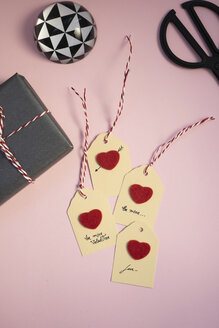 Valentine gift, paperweight, self-made tags and scissors on pink background - MOMF00606