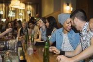 Homosexual couple hugging and drinking at bar - HEROF12129