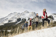 Friends snowshoeing below snowy mountains - HEROF12150
