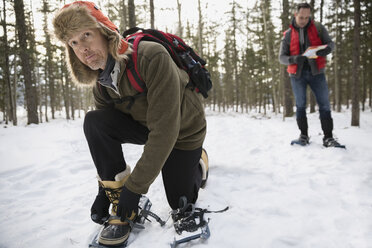 Man putting on snowshoes in snowy woods - HEROF12174
