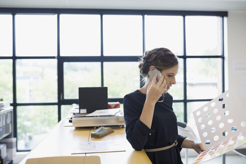 Female designer talking on cell phone looking at brochure in office - HEROF12231