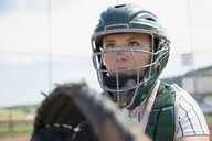 Focused middle school girl softball catcher wearing helmet - HEROF12261