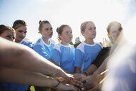 Focused middle school girl soccer team joining hands in huddle - HEROF12264