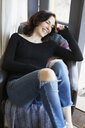 Laughing mature brunette woman wearing ripped jeans and sweater - HEROF12282
