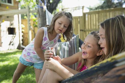 Girls using cell phone in hammock in backyard - HEROF12297