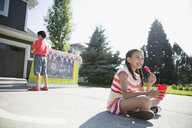 Girl eating flavored ice and drinking lemonade in front of lemonade stand in sunny driveway - HEROF12333