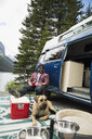 Man and dog relaxing outside camper van at remote lakeside - HEROF12336