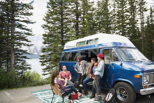 Friends hanging out talking outside camper van at remote lakeside - HEROF12342 - Hero Images/Westend61