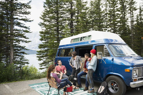 Friends hanging out talking outside camper van at remote lakeside - HEROF12342