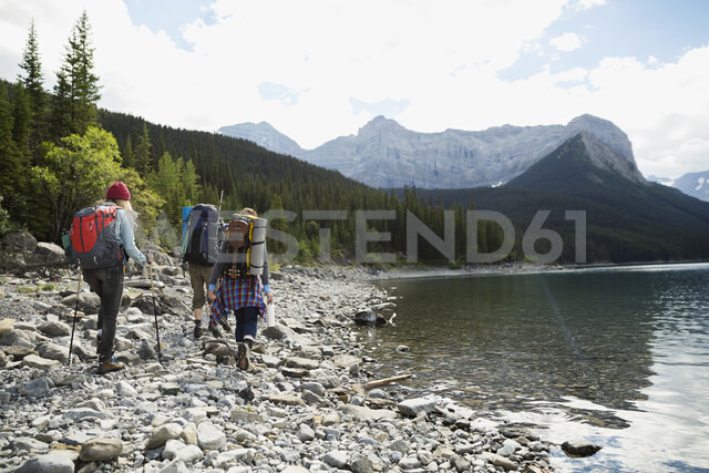 Female friends hiking with backpacks and hiking poles along craggy remote lake - HEROF12351 - Hero Images/Westend61