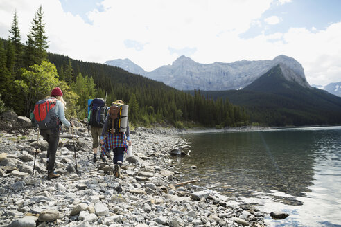 Female friends hiking with backpacks and hiking poles along craggy remote lake - HEROF12351