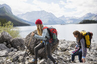 Female friends hiking with backpacks and hiking poles at craggy remote mountain lakeside - HEROF12354