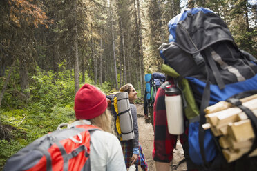 Friends with backpacks and camping equipment hiking on trail in woods - HEROF12360
