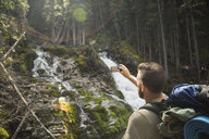 Man hiking with backpack photographing waterfall in woods with camera phone - HEROF12363