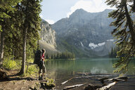 Female hiker with backpack enjoying tranquil, remote mountain lake view - HEROF12369