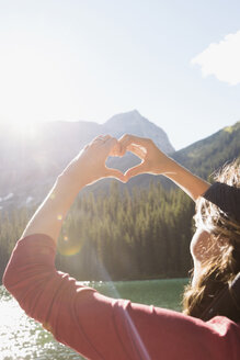Female hiker gesturing heart-shape at sunny mountain lakeside - HEROF12372