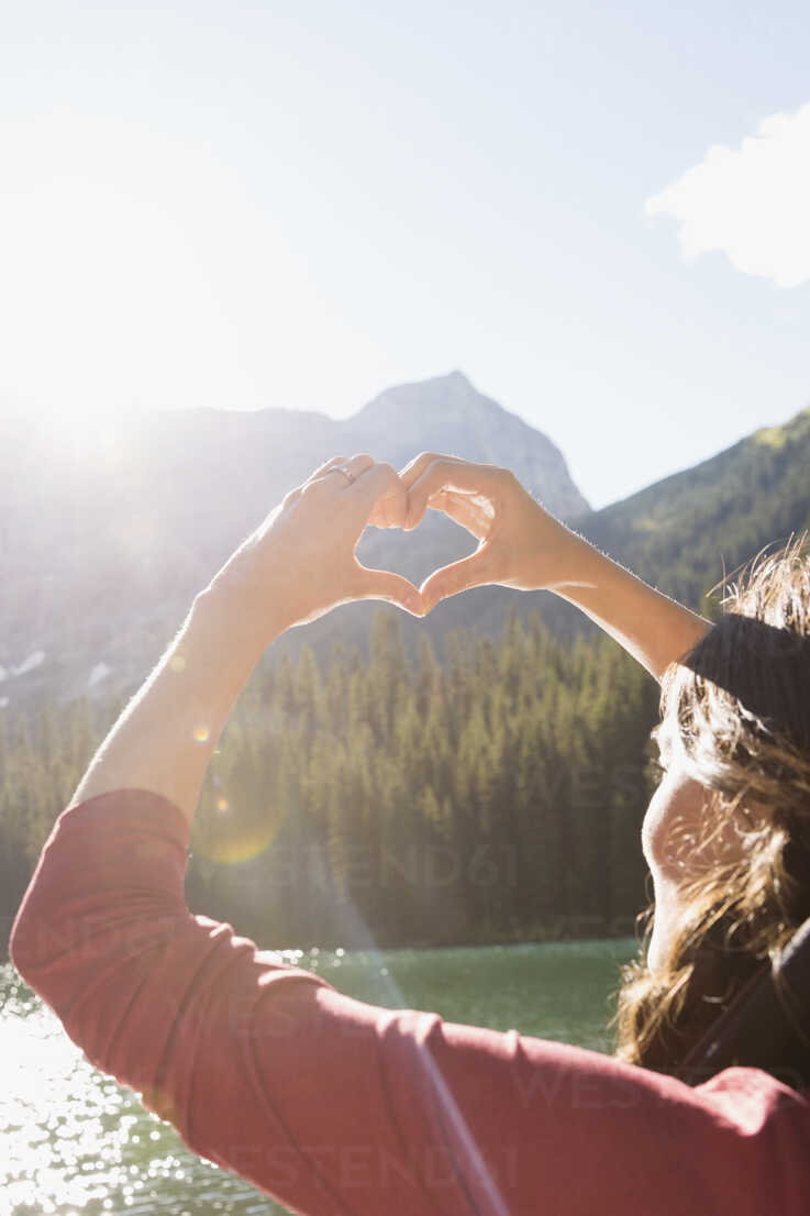 Female hiker gesturing heart-shape at sunny mountain lakeside - HEROF12372 - Hero Images/Westend61