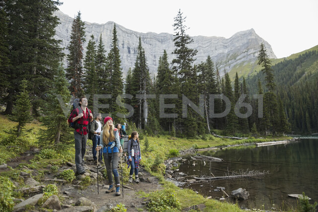 Friends hiking along lake on trail below mountains in remote woods - HEROF12378