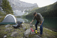 Man cooking with camping stove at remote mountain lakeside campsite - HEROF12381