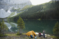 Male friends camping at remote mountain lakeside campsite - HEROF12384