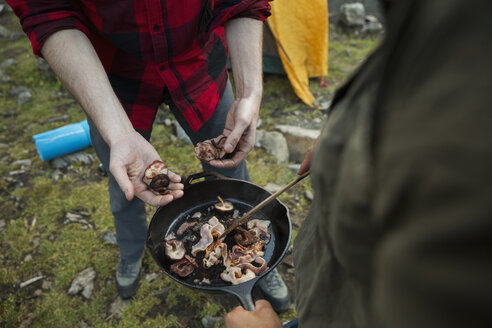 Male friends cooking bacon in skillet at campsite - HEROF12387