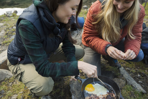 Female friends cooking eggs and bacon in skillet at campsite - HEROF12390