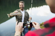 Man photographing friend fishing catching fish at lakeside - HEROF12393