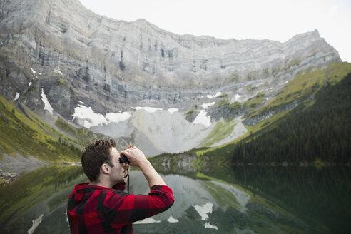 Man at remote lakeside using binoculars looking up at remote mountain - HEROF12396