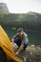 Man pitching tent at remote lakeside campsite - HEROF12402