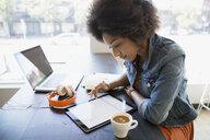 Focused woman working at digital tablet in cafe - HEROF12417