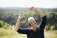 Female cancer survivor with shaved head dancing listening to music with headphones on sunny remote hilltop - HEROF12432