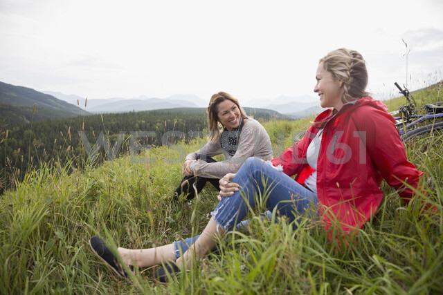 Female friends relaxing in grass in remote rural field - HEROF12435