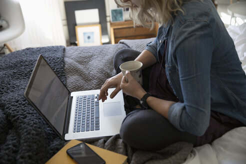 Young woman drinking coffee and using laptop on bed - HEROF12441