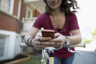 Young woman with bicycle texting with smart phone on sidewalk - HEROF12453