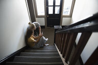 Young couple using smart phone on apartment stairs - HEROF12459
