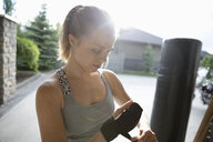 Young woman practicing martial arts, tightening wrist wrap in sunny driveway - HEROF12522