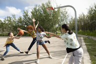 Teenage girl friends playing basketball at park basketball court - HEROF12528