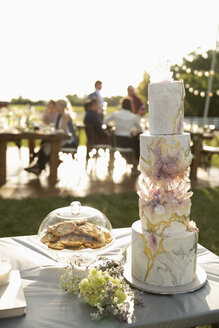 Tiered wedding cake and flowers on patio table - HEROF12537