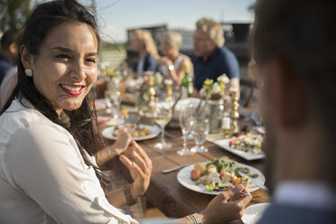 Woman smiling, eating and talking with friend at sunny garden party lunch - HEROF12540
