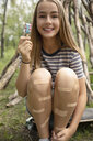 Portrait smiling tween girl with bandages on legs eating flavored ice - HEROF12618